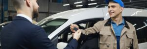 Man Giving Keys To Auto Service Worker